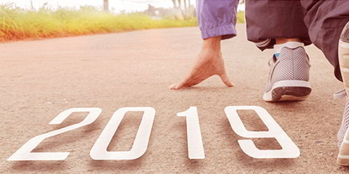 "Runner poised to begin a race; the text ""2019"" sits on the ground beneath them."