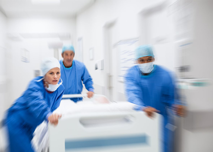 Team of doctors rushing a patient into a hospital ER after testing troponin levels