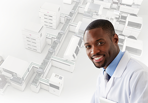 Young man in a medical laboratory coat smiling with the DxA 5000 Automation system in the background
