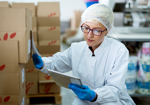 Laboratory supervisor performing manual inventory counting boxes with a laboratory inventory management system