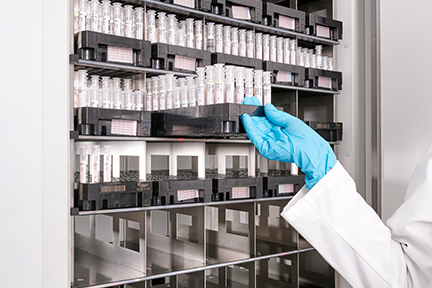 A gloved hand retrieves an orderly rack of tubes from DxA 5000 storage shelves