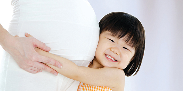 Child hugging pregnant woman