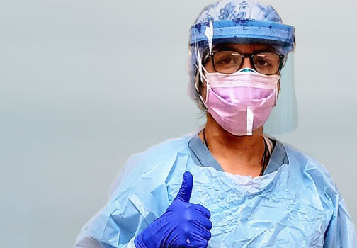 Front line care worker in scrubs an protective mask